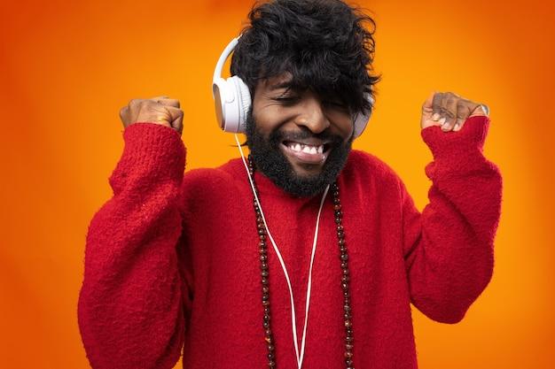Uomo afroamericano che ascolta con gioia la musica contro la superficie arancione
