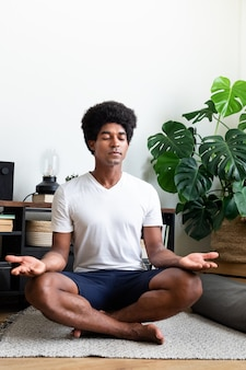 L'uomo afroamericano medita nel suo appartamento copia spazio immagine verticale meditazionespiritualità