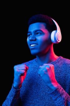 Ritratto di uomo afroamericano isolato su nero in luce al neon multicolore