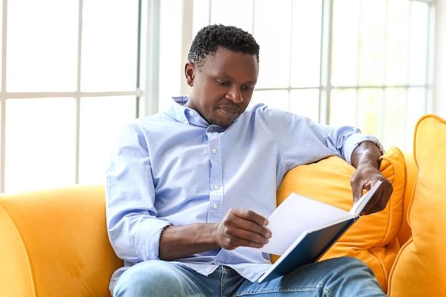 Uomo afroamericano che legge un libro a casa