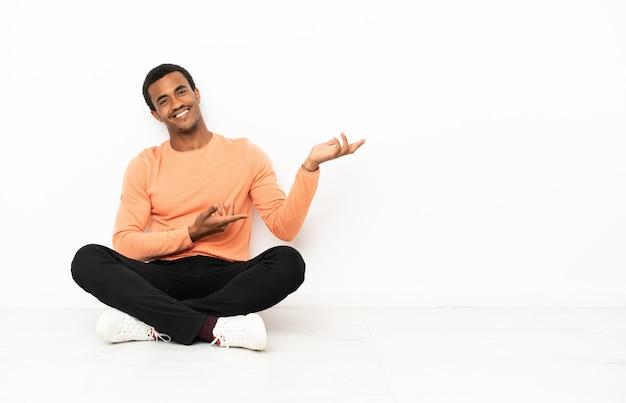 Uomo afroamericano seduto sul pavimento su sfondo copyspace isolato che estende le mani di lato per invitare a venire