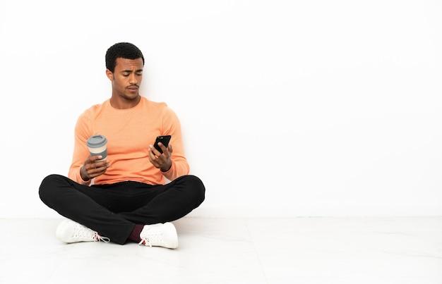 Uomo afroamericano seduto sul pavimento su sfondo copyspace isolato tenendo il caffè da portare via e un cellulare a