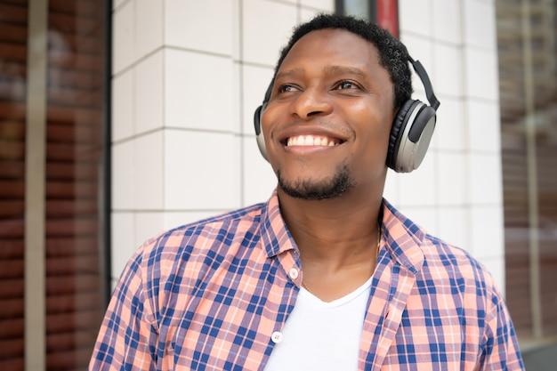 Uomo afroamericano sorridente e ascolto di musica con le cuffie stando in piedi all'aperto sulla strada.