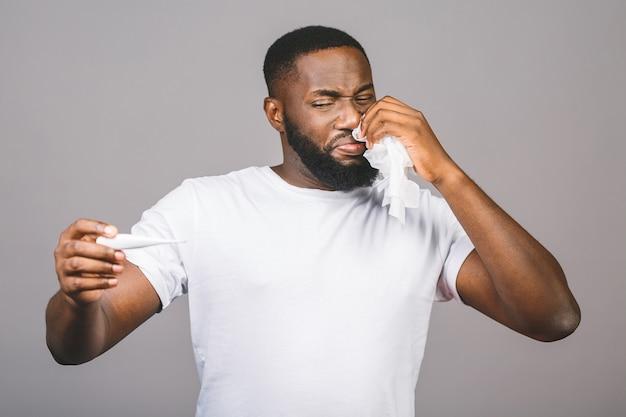 Uomo afroamericano che controlla fondo grigio isolato, malattia e febbre, influenza e raffreddore, virus malato, facendo uso del termometro.