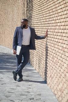 Un uomo afroamericano in giacca e cravatta in piedi vicino al muro di mattoni