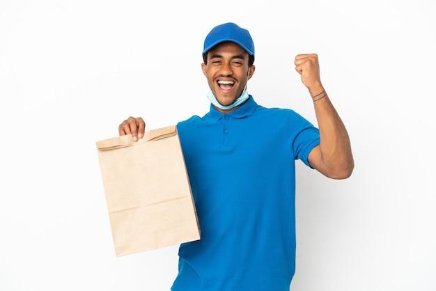 Uomo afroamericano che prende un sacchetto di cibo da asporto isolato su sfondo bianco per celebrare una vittoria