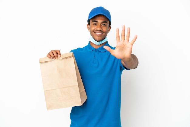 Uomo afroamericano che prende un sacchetto di cibo da asporto isolato su sfondo bianco contando cinque con le dita