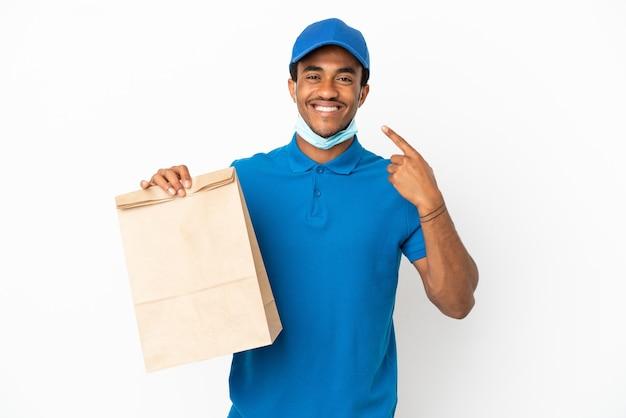 Uomo afroamericano che prende un sacchetto di cibo da asporto isolato su sfondo bianco dando un gesto di pollice in alto