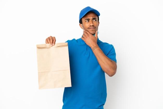 Uomo afroamericano che prende un sacchetto di cibo da asporto isolato su sfondo bianco avendo dubbi