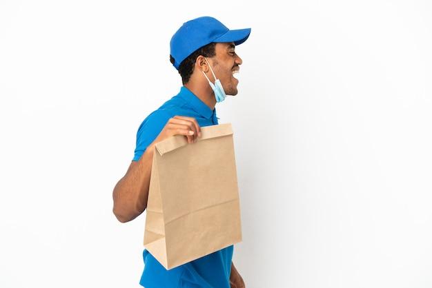 Uomo afroamericano che prende un sacchetto di cibo da asporto isolato su sfondo bianco ridendo in posizione laterale