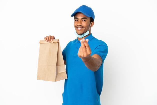 Uomo afroamericano che prende un sacchetto di cibo da asporto isolato su sfondo bianco che fa gesto di denaro