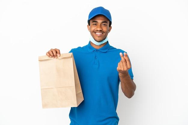 Uomo afroamericano che prende un sacchetto di cibo da asporto isolato su sfondo bianco facendo gesto di soldi