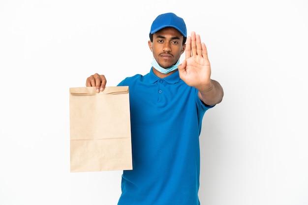 Uomo afroamericano che prende un sacchetto di cibo da asporto isolato su sfondo bianco facendo un gesto di arresto