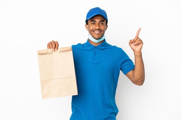 Uomo afroamericano che prende un sacchetto di cibo da asporto isolato su sfondo bianco che indica una grande idea