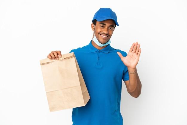Uomo afroamericano che prende un sacchetto di cibo da asporto isolato su sfondo bianco salutando con la mano con espressione felice