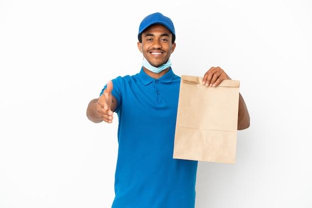 Uomo afroamericano che prende un sacchetto di cibo da asporto isolato su sfondo bianco che stringe la mano per chiudere un buon affare