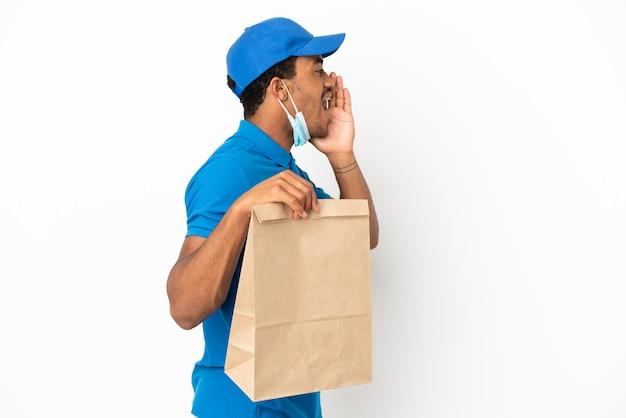 Uomo afroamericano che prende un sacchetto di cibo da asporto isolato su sfondo bianco che grida con la bocca spalancata di lato