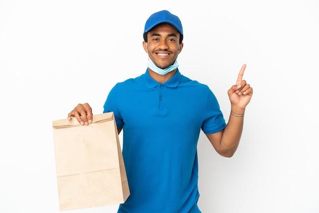Uomo afroamericano che prende un sacchetto di cibo da asporto isolato su sfondo bianco che mostra e solleva un dito in segno del meglio