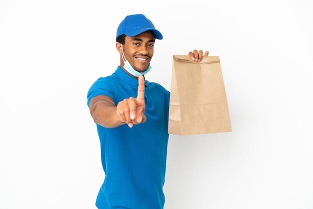 Uomo afroamericano che prende un sacchetto di cibo da asporto isolato su sfondo bianco che mostra e solleva un dito
