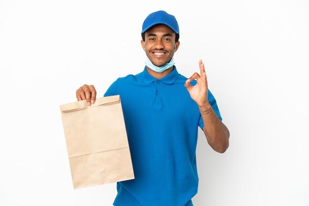 Uomo afroamericano che prende un sacchetto di cibo da asporto isolato su sfondo bianco che mostra segno ok con le dita