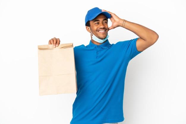 Uomo afroamericano che prende un sacchetto di cibo da asporto isolato su sfondo bianco sorridendo molto