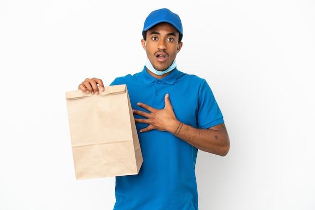 Uomo afroamericano che prende un sacchetto di cibo da asporto isolato su sfondo bianco sorpreso e scioccato mentre guarda a destra