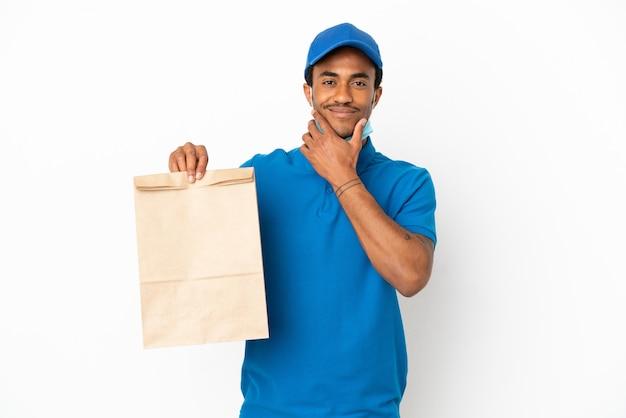 Uomo afroamericano che prende un sacchetto di cibo da asporto isolato su sfondo bianco pensando