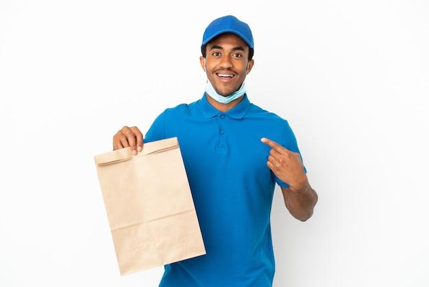 Uomo afroamericano che prende un sacchetto di cibo da asporto isolato su sfondo bianco con espressione facciale a sorpresa