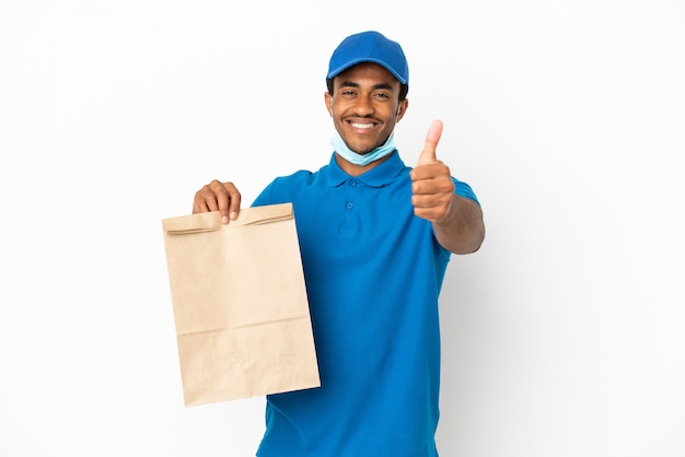 Uomo afroamericano che prende un sacchetto di cibo da asporto isolato su sfondo bianco con il pollice in alto perché è successo qualcosa di buono