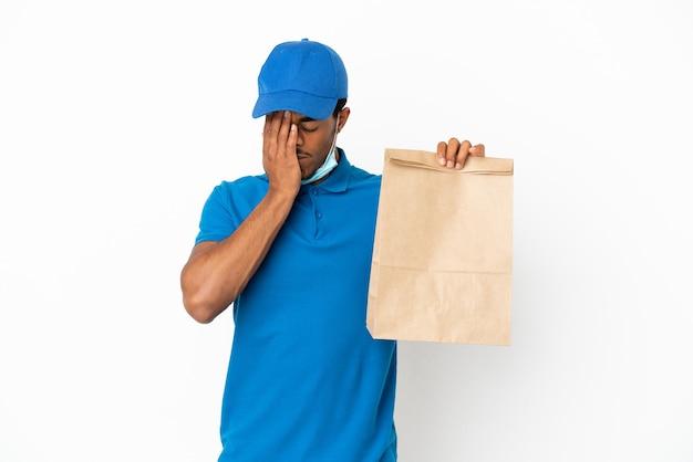 Uomo afroamericano che prende un sacchetto di cibo da asporto isolato su sfondo bianco con espressione stanca e malata