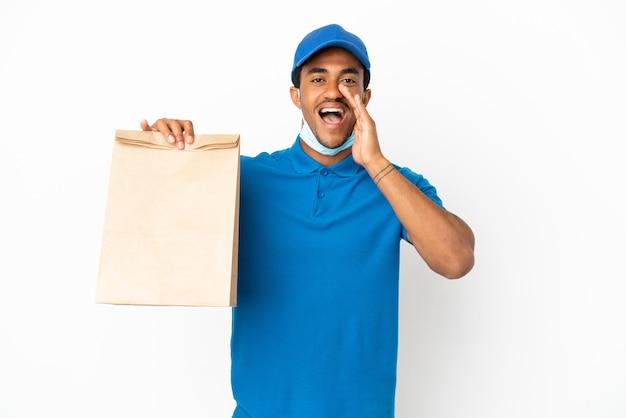 Uomo afroamericano che prende un sacchetto di cibo da asporto isolato sul muro bianco che grida con la bocca spalancata