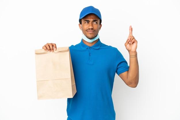 Uomo afroamericano che prende un sacchetto di cibo da asporto isolato su un muro bianco con le dita incrociate e augurando il meglio