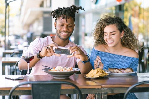 Uomo afroamericano che scatta foto al cibo mentre pranza con la sua ragazza in un ristorante.