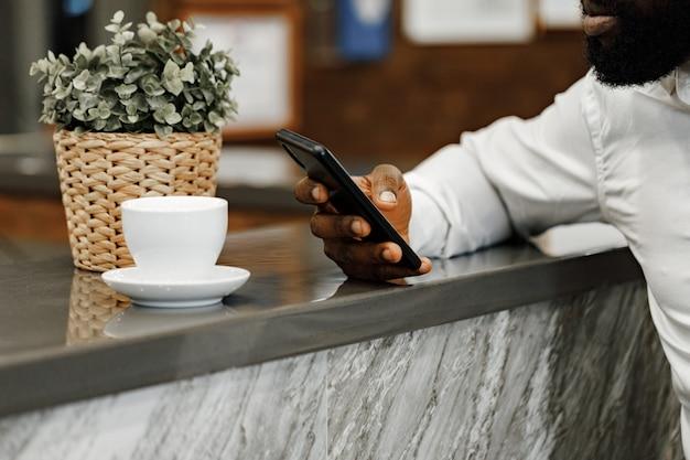 Uomo afroamericano che utilizza il suo smartphone vicino alla reception in hotel si chiuda
