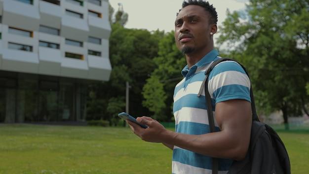 Uomo afroamericano che utilizza smartphone camminando in città bel giovane con zaino che comunica su smartphone tecnologia mobile ritratto all'aperto