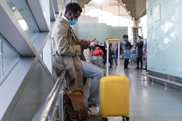 Uomo afroamericano che indossa la maschera per il viso in aeroporto