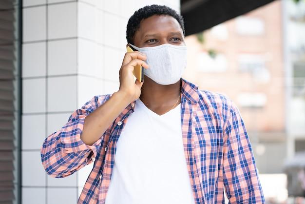 Uomo afroamericano che indossa una maschera e parla al telefono mentre si cammina all'aperto per strada. nuovo concetto di stile di vita normale. Foto Premium
