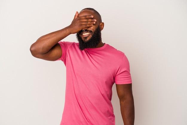 L'uomo afroamericano con la barba isolato su sfondo rosa copre gli occhi con le mani, sorride ampiamente in attesa di una sorpresa.