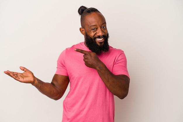 Uomo afroamericano con barba isolato su sfondo rosa eccitato in possesso di uno spazio copia sul palmo.