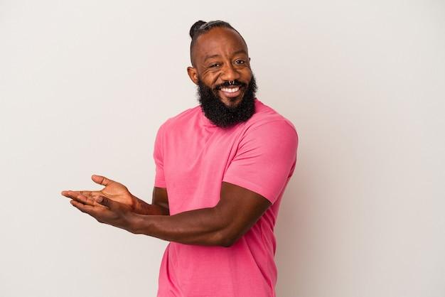Uomo afroamericano con la barba isolato su sfondo rosa che tiene uno spazio di copia su un palmo.