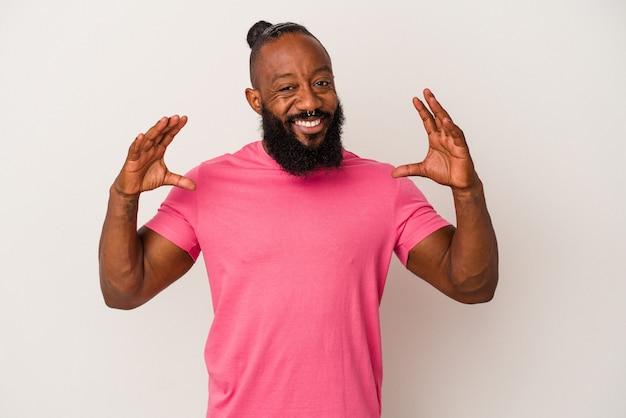Uomo afroamericano con la barba isolato su sfondo rosa che tiene qualcosa con le palme, offrendo alla macchina fotografica.