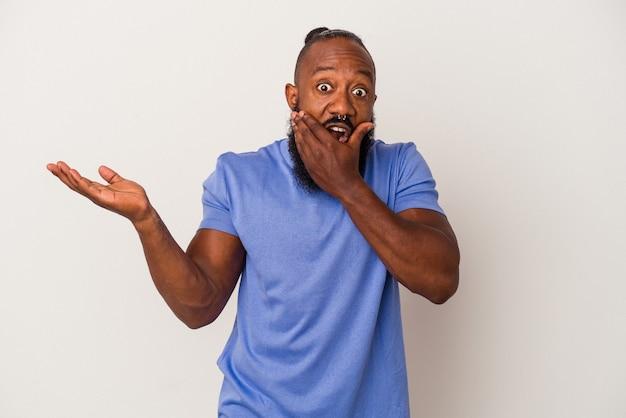 L'uomo afroamericano con la barba isolato su sfondo rosa tiene lo spazio della copia su un palmo, tiene la mano sulla guancia. stupito e deliziato.