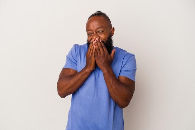 Uomo afroamericano con la barba isolato su sfondo rosa che ride di qualcosa, coprendo la bocca con le mani.