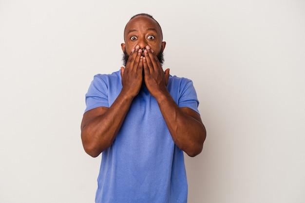 Uomo afroamericano con la barba isolato su sfondo rosa scioccato che copre la bocca con le mani.