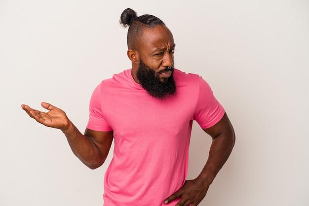 Uomo afroamericano con barba isolato su sfondo rosa che mostra uno spazio di copia su un palmo e tiene un'altra mano sulla vita.