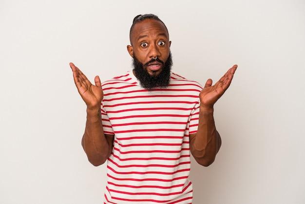 Uomo afroamericano con la barba isolato su sfondo rosa sorpreso e scioccato.