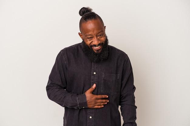L'uomo afroamericano con la barba isolato su sfondo rosa tocca la pancia, sorride dolcemente, mangia e soddisfa il concetto.