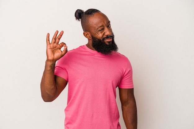 L'uomo afroamericano con la barba isolato su sfondo rosa strizza l'occhio e tiene un gesto ok con la mano.