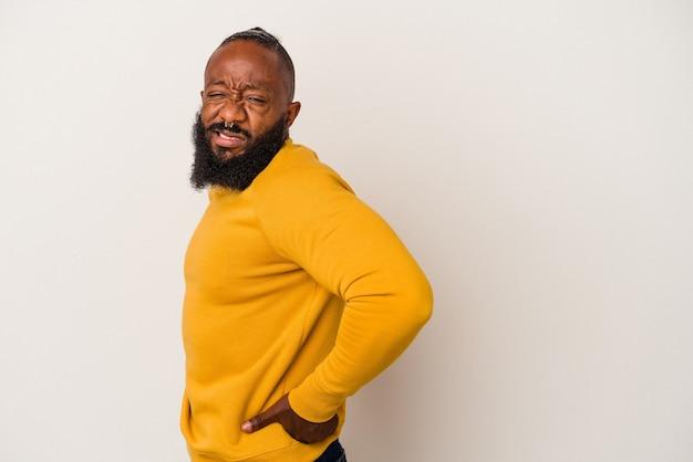 Uomo afroamericano con la barba isolata sulla parete rosa che soffre di mal di schiena.
