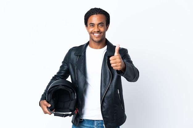 Uomo afroamericano con le trecce che tiene un casco del motociclo isolato sul muro bianco con i pollici in su perché è successo qualcosa di buono